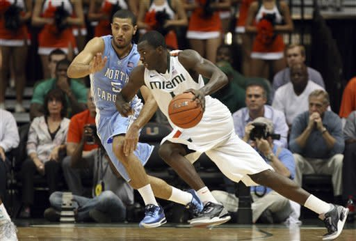 Miami's Durand Scott, right, drives to the basket as North Carolina's Kendall Marshall (5) defends during the first half of an NCAA college basketball game, Wednesday, Feb. 15, 2012, in Coral Gables, Fla. (AP Photo/Lynne Sladky)
