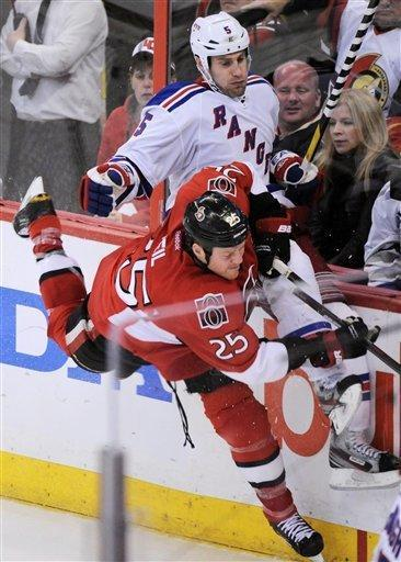 Ottawa Senators' Chris Neil slams New York Rangers' Dan Girardi into the boards during the third period of Game 4 of a first-round NHL hockey Stanley Cup playoff series against the Ottawa Senators in Ottawa, Ontario, Wednesday, April 18, 2012. (AP Photo/The Canadian Press, Sean Kilpatrick)