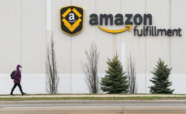 A person walks outside the Amazon fulfilment centre in Brampton, Ont., on April 20. In a statement to CBC News on Saturday, Amazon said three shifts at its Brampton facility and one shift at its centre in Bolton, Ont., are being temporarily suspended due to COVID-19 outbreaks.