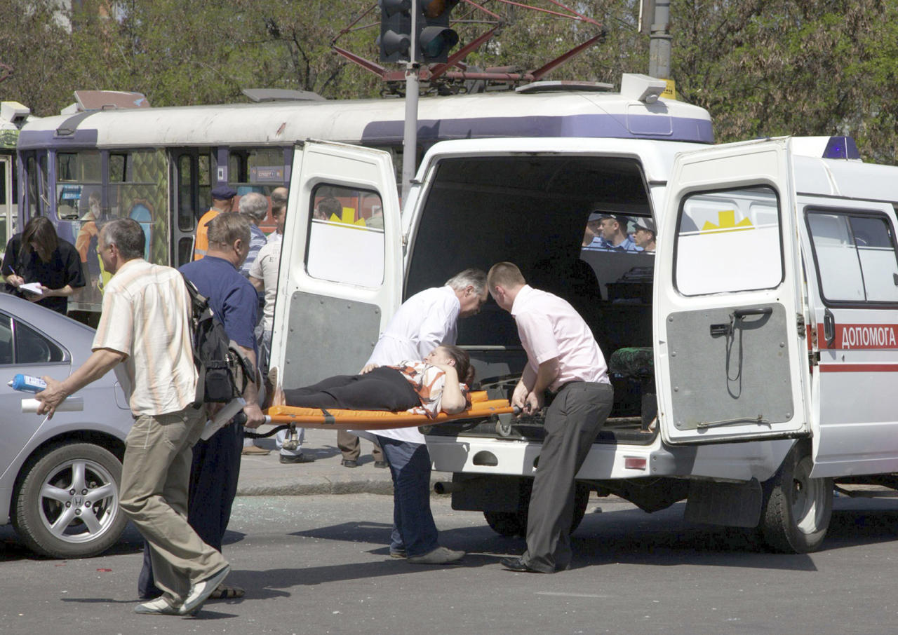 People assist injured after an explosion in Dnipropetrovsk, Ukraine, Friday, April 27, 2012. Ukraine officials say dozens of people including schoolchildren, were injured in four blasts in the eastern Ukrainian city. (AP Photo/Dmitriy Dvorsky)