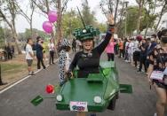 """A supporter of the anti-military Future Forward Party in a costume of a military-tank participates in a run dubbed as """"Run Against Dictatorship"""" at a park in Bangkok, Thailand, Sunday, Jan. 12, 2020. About 6000 runners participated in a 3 kilometer run to demonstrate against the government led by former army general Prayuth Chan-ocha. (AP Photo/Gemunu Amarasinghe)"""