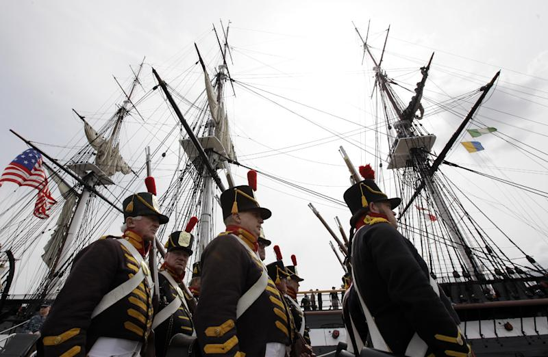 Military reenactors in the uniforms of U.S. Marines from the war of 1812 march in front of the USS Constitution moments after the vessel arrived at her berth in Charlestown Navy Yard, in Boston, Sunday, Aug. 19, 2012. The U.S. Navy's oldest commissioned war ship sailed under her own power Sunday for the first time since 1997. The sail was held to commemorate the 200th anniversary of the ship's victory over HMS Guerriere in the War of 1812. (AP Photo/Steven Senne)