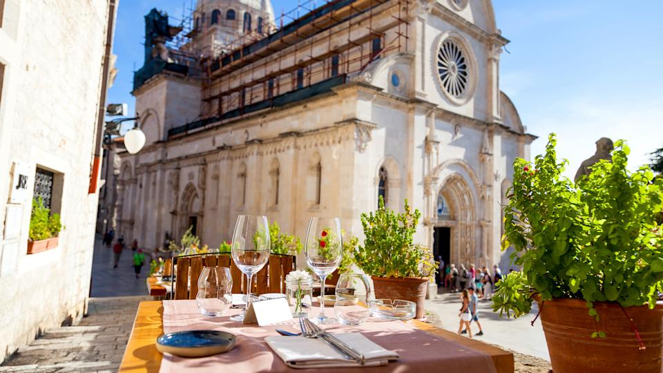 Croatia, Elegant restaurant table waiting for customers, How Much to Tip When Traveling to These 25 Countries, outdoor terrace in the old town of Sibenik