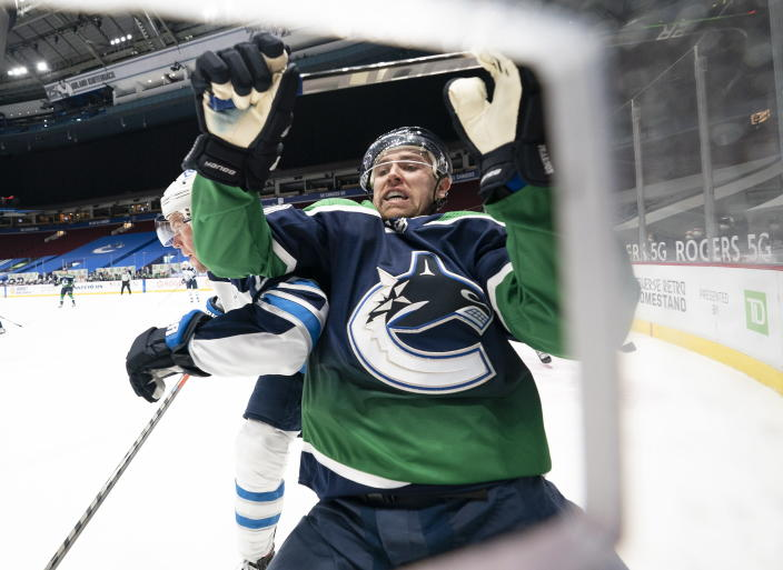 Vancouver Canucks left wing Tanner Pearson, right, goes into the boards with Winnipeg Jets defenseman Dylan DeMelo (2) during second-period NHL hockey game action in Vancouver, British Columbia, Sunday, Feb. 21, 2021. (Jonathan Hayward/The Canadian Press via AP)
