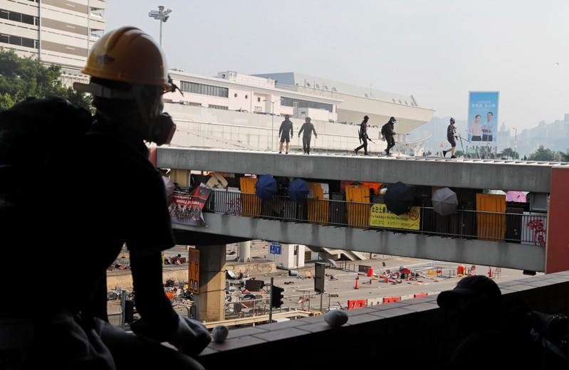 Protesters walk on a bridge that runs over the entrance to the Cross Harbour Tunnel in Hong Kong