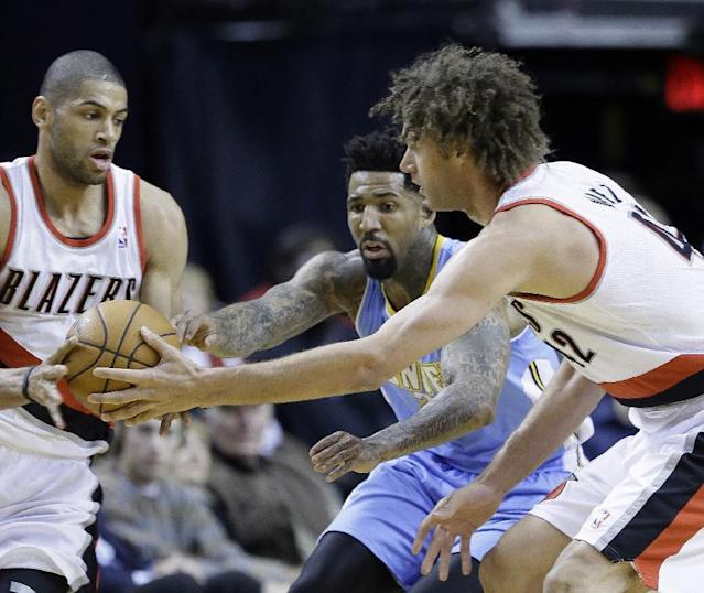 Portland Trails Blazers center Robin Lopez, right, passes off to teammate Nicolas Batum, from France, left, as Denver Nuggets forward Wilson Chandler defends during the first half of an NBA basketball game in Portland, Ore., Thursday, Jan. 23, 2014. (AP Photo/Don Ryan)
