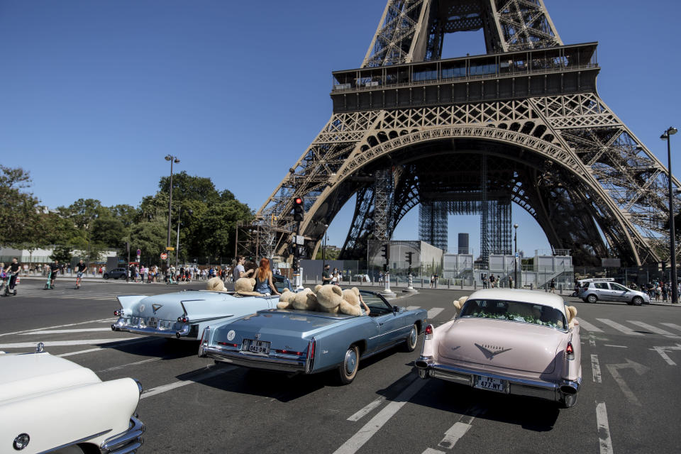 Teddy bears, set up by Philippe Labourel, who wants to be named 'Le papa des nounours' (Teddy Bears father) are pictured inside American vintage cars driving through Paris, Sunday, June, 13, 2021. The event took place in a show of support for the tourism industry which was hit by the COVID-19 pandemic. (AP Photo/Lewis Joly)