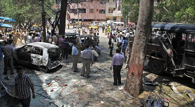 Indian police gather at the scene of a blast near the Bharatiya Janata Party (BJP) office in Bangalore on April 17, 2013. Police in the southern city of Bangalore said Wednesday they were investigating a minor blast outside the office of a political party which injured 12 people.