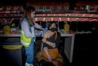 A woman receives a dose of the AstraZeneca vaccine, during a mass vaccination campaign at Wanda Metropolitano stadium in Madrid, Spain, Wednesday, March 24, 2021. Spain resumed the use of the AstraZeneca vaccine on Wednesday by extending it to adults up to 65 years old. (AP Photo/Manu Fernandez)