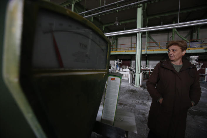 """Vidosava Jovanovic, an employee of the detergent factory """"Dita"""" looks at her former work place inside the factory in the Bosnian town of Tuzla, 140 kms north of Sarajevo on Wednesday, Feb. 12, 2014. The violence engulfing Bosnia in recent days, with scenes of burning government buildings and protesters pelting police with stones, has many root causes. One of them is the failed privatizations of state-owned companies. (AP Photo/Amel Emric)"""