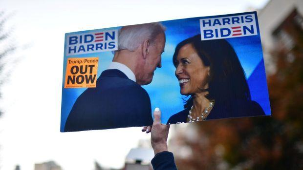 An activist holds a sign showing Democratic presidential nominee Joe Biden and vice presidential nominee Kamala Harris in Philadelphia