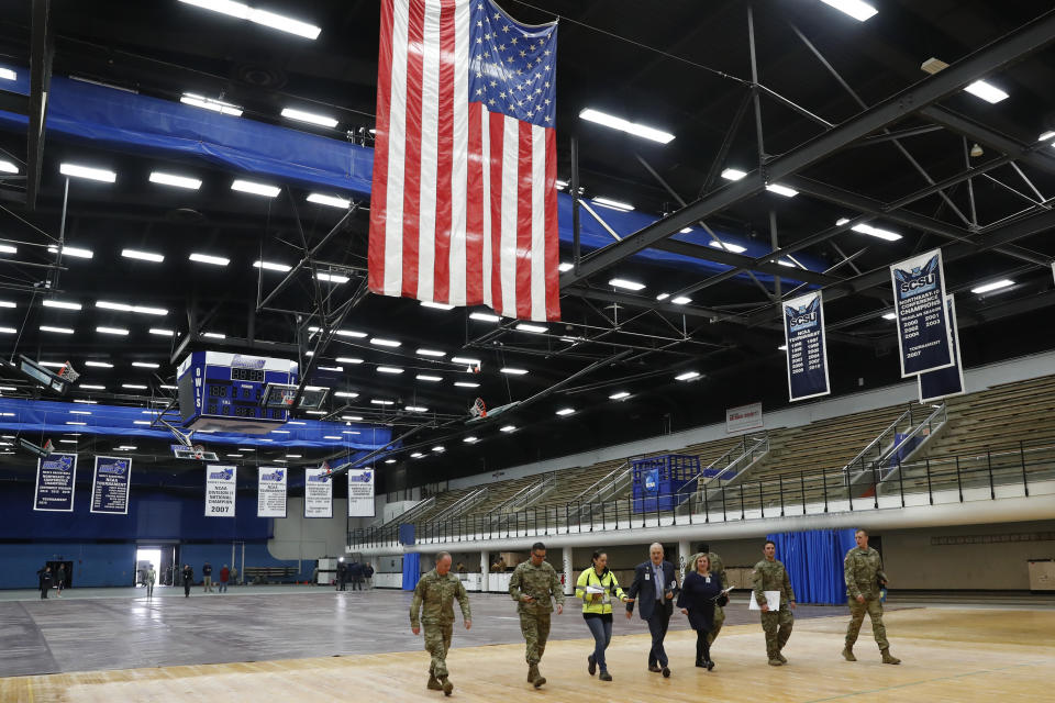 """National Guard personnel join Yale New Haven Health officials walk across the court at Southern Connecticut State University's Moore Field House as they prepare to survey supplies delivered by FEMA for a """"surge"""" hospital to help out during the current coronavirus crisis, Tuesday, March 31, 2020, in New Haven, Conn. The 250-bed field hospital will facilitate overflow in the event that regional hospitals treating COVID-19 patients reach their capacity. (AP Photo/Kathy Willens)"""