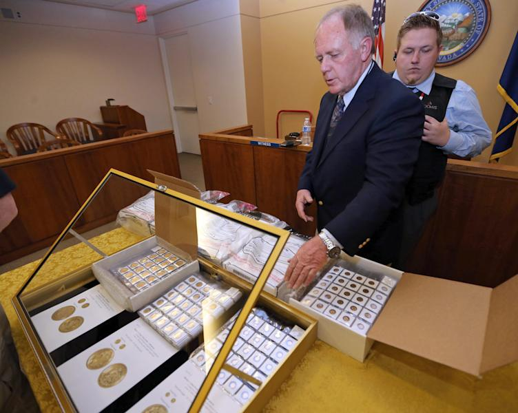 FILE - In this Feb. 26, 2013 file photo, appraiser Howard Herz shows gold coins once belonging to Walter Samaszko, Jr. that were up for auction in Carson City, Nev. Samaszko, 69, died in June, 2012, leaving thousands of gold coins and bouillon in his garage. One batch, mostly bullion, was sold at auction in February for $3.5 million. Another auction Tuesday, Aug. 6, 2013 at the Carson City courthouse includes more than 2,600 coins to be sold in six lots. (AP Photo/Las Vegas Review-Journal, Cathleen Allison, File) LOCAL TV OUT; LOCAL INTERNET OUT; LAS VEGAS SUN OUT