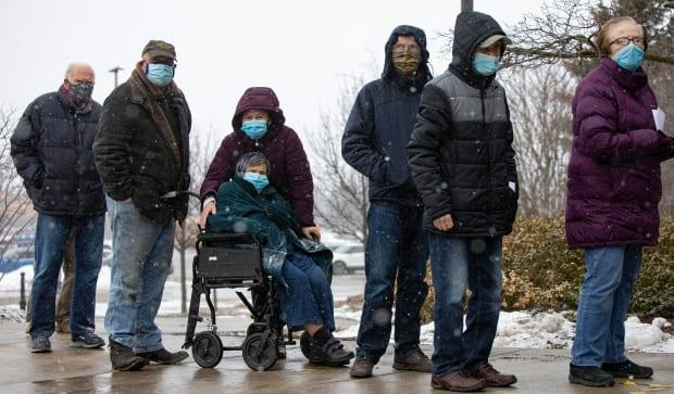 People aged 80 and older line up outside a sports centre in Richmond Hill, Ont. on Monday to be among the first participants in York Region's mass vaccination program against COVID-19.