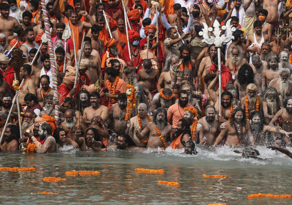 FILE - In this April 12, 2021, file photo, Hindu holy men take dips in the Ganges River during Kumbh Mela, or pitcher festival, one of the most sacred pilgrimages in Hinduism, in Haridwar, northern state of Uttarakhand, India. Despite clear signs that India was being swamped by another surge of coronavirus infections, Prime Minister Narendra Modi refused to cancel the festival, along with campaign rallies and cricket matches with spectators. The burgeoning crisis has badly dented Modi's carefully cultivated image as an able technocrat. (AP Photo/Karma Sonam, File)