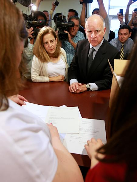 Gov. Jerry Brown and his wife, Anne Gust Brown watch Sacramento Registrar of Voters employees Jennifer Little, left, and Kristen Larsen, right, look over the papers for Brown's tax-hike initiative petitions he submitted at the Sacramento County Registrar of Voters office in Sacramento, Calif., Thursday, May 10, 2012. More than 1.5 million signatures were collected to place Brown's initiative on November ballot. Brown has warned that if voters do not pass the tax hikes there would be even deeper cuts to schools, higher education and social services.(AP Photo/Rich Pedroncelli)
