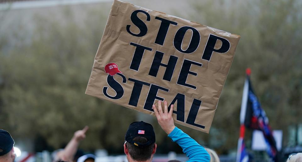 A Trump support holds Stop the Steal sign in protest of votes being counted.