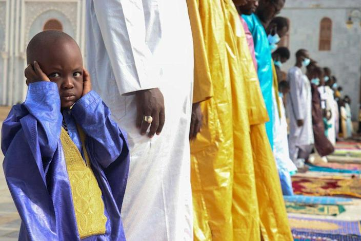 A boy covers his ears during prayers at the mosque.