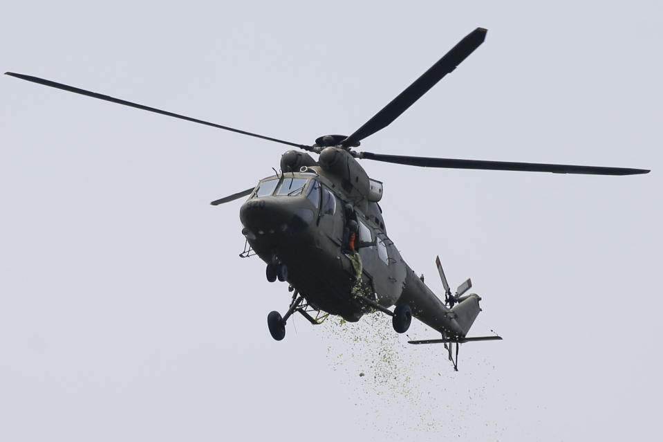 A military helicopter drops yellow confetti during the state burial rites of former Philippine President Benigno Aquino III on Saturday, June 26, 2021 at a memorial park in suburban Paranaque city, Philippines. Aquino was buried in austere state rites during the pandemic Saturday with many remembering him for standing up to China over territorial disputes, striking a peace deal with Muslim guerrillas and defending democracy in a Southeast Asian nation where his parents helped topple a dictator. He was 61. (AP Photo/Aaron Favila)