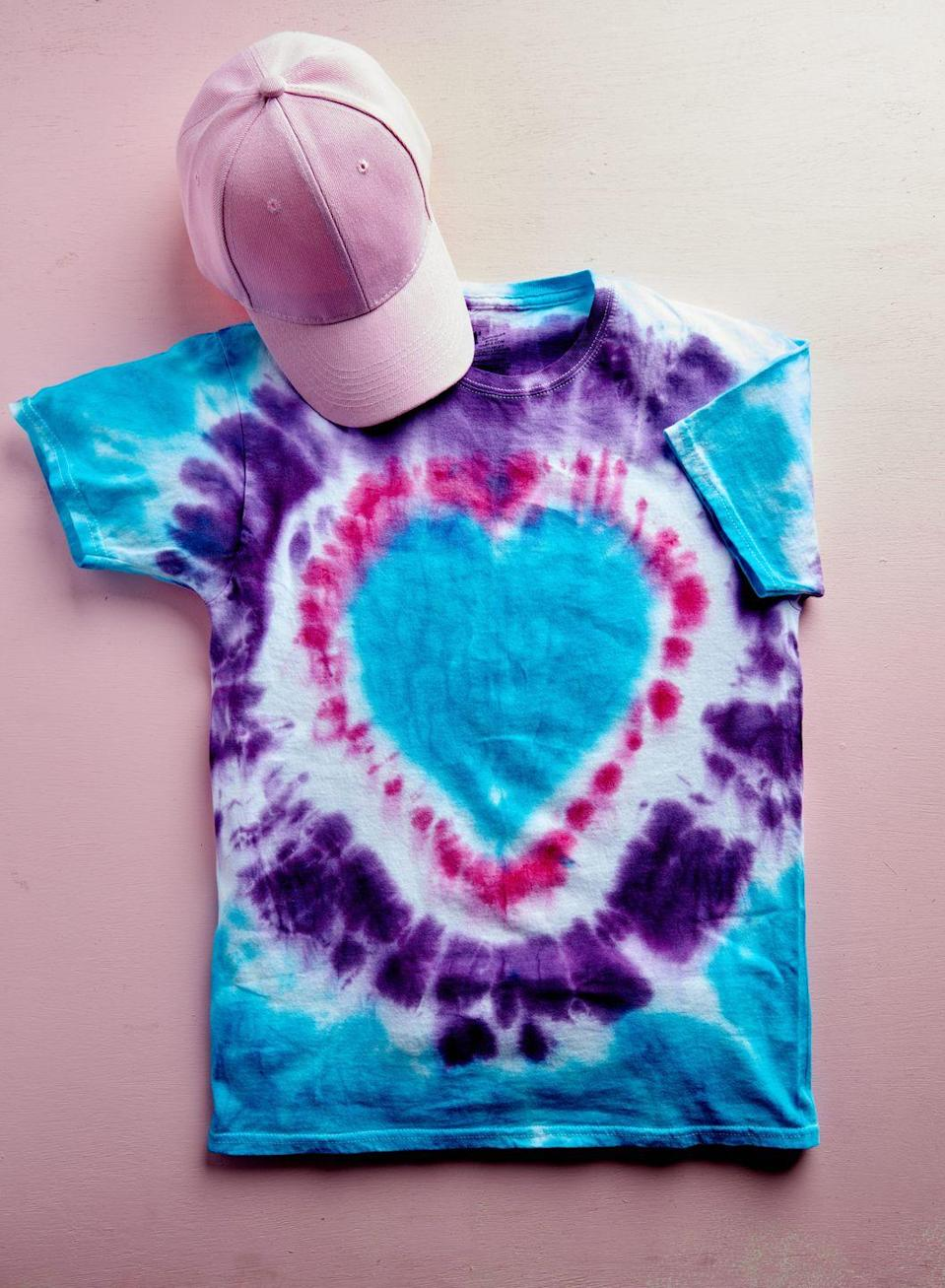 "<p>Create some high-fashion for the big day by creating a custom tie dye T-shirt.</p><p><strong>To make:</strong> Start by washing a 100% cotton T-shirt. While still damp, fold the shirt in half. Using a chalk pencil or disappearing pen, draw an exaggerated heart on half of the shirt, starting and ending at the fold. Pleat the shirt, lining up the heart line (once pleated the line should be straight). Use a zip tie or rubber band to hold pleats together. Create more pleats along the remaining shirt, holding in place with zip ties or rubber bands. Place different color dyes in separate squeeze bottles (you will need as many colors ass pleated sections). Start by squeezing dye on heart section stopping 1/2 inch from the zip tie. Continue dying, using a another color between each zip tie. Allow to dry completely then remove ties.</p><p><a class=""link rapid-noclick-resp"" href=""https://www.amazon.com/s?k=rit+dye&tag=syn-yahoo-20&ascsubtag=%5Bartid%7C10050.g.1584%5Bsrc%7Cyahoo-us"" rel=""nofollow noopener"" target=""_blank"" data-ylk=""slk:SHOP DYE"">SHOP DYE</a></p>"
