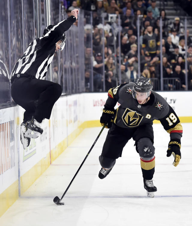 Linesman Brandon Gawryletz jumps to avoid contact against Vegas Golden Knights right wing Reilly Smith (19) as he skates with the puck against the Buffalo Sabres during the second period of an NHL hockey game, Tuesday, Oct. 16, 2018, in Las Vegas. (AP Photo/David Becker)