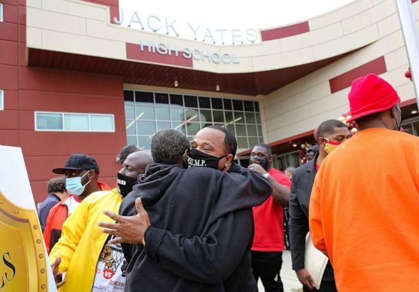 PHOTO: Members of George Floyd's high school football team hug family members during a A Black History Month tribute to George Floyd and the Black Lives Matter movement at Jack Yates High School in Houston, Texas, Feb. 6, 2021.  (Elizabeth Conley/Houston Chronicle via AP)