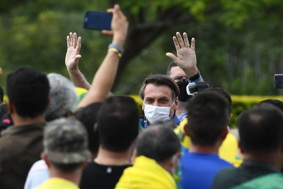 Brazilian President Jair Bolsonaro waves at supporters who gathered outside the lawns of the Alvorada Palace to celebrate his birthday, in Brasilia, on March 21, 2021. (Photo by EVARISTO SA / AFP) (Photo by EVARISTO SA/AFP via Getty Images)