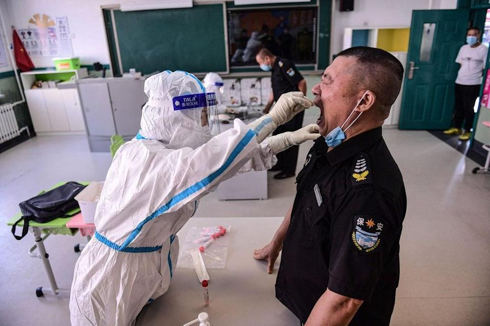 A primary school staff member undergoes a Covid test in Shenyang, China  (AFP via Getty Images)