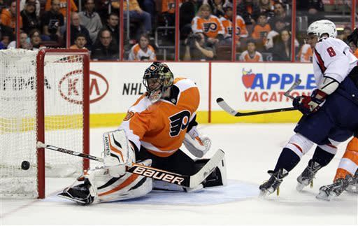 Philadelphia Flyers' Ilya Bryzgalov, left, watches the puck shot by Washington Capital Alex Ovechkin, right, go wide of the net in the first period of an NHL hockey game, Sunday, March 31, 2013, in Philadelphia. (AP Photo/Tom Mihalek)