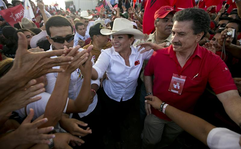 In this Sunday, Nov. 17, 2013 photo, Free Party presidential candidate Xiomara Castro greets supporters during her closing campaign rally in Tegucigalpa, Honduras. Castro, the wife of ousted President Manuel Zelaya, is a frontrunner in the Nov. 24 presidential election. (AP Photo/Eduardo Verdugo)