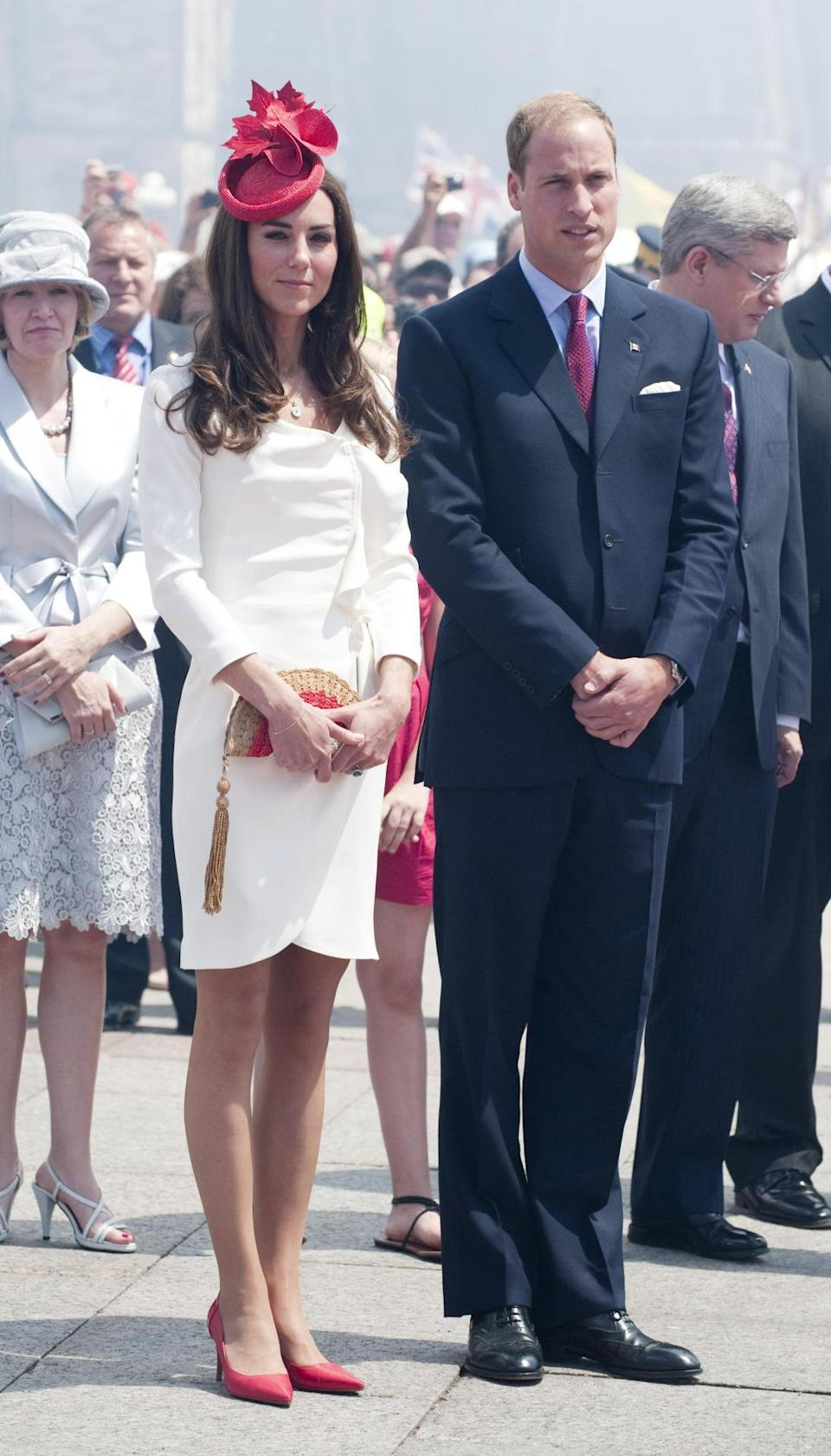 <p>For Canada Day, Kate opted for a white dress from Reiss paired with a red Lock & Co fascinator, Anya Hindmarch's fan clutch and red heels from Hobbs.</p><p><i>[Photo: PA]</i></p>
