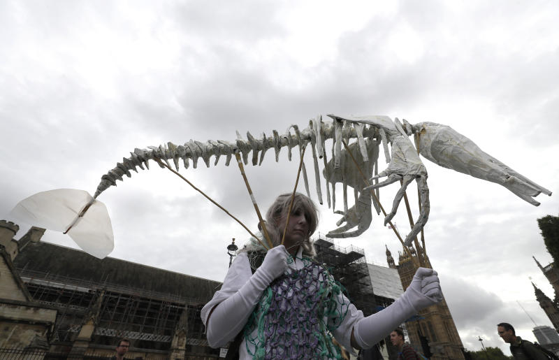 A protestor carries a pretend skeleton near Parliament in London, Tuesday, Oct. 8, 2019. Police are reporting they have arrested more than 300 people at the start of two weeks of protests as the Extinction Rebellion group attempts to draw attention to global warming. (AP Photo/Kirsty Wigglesworth)