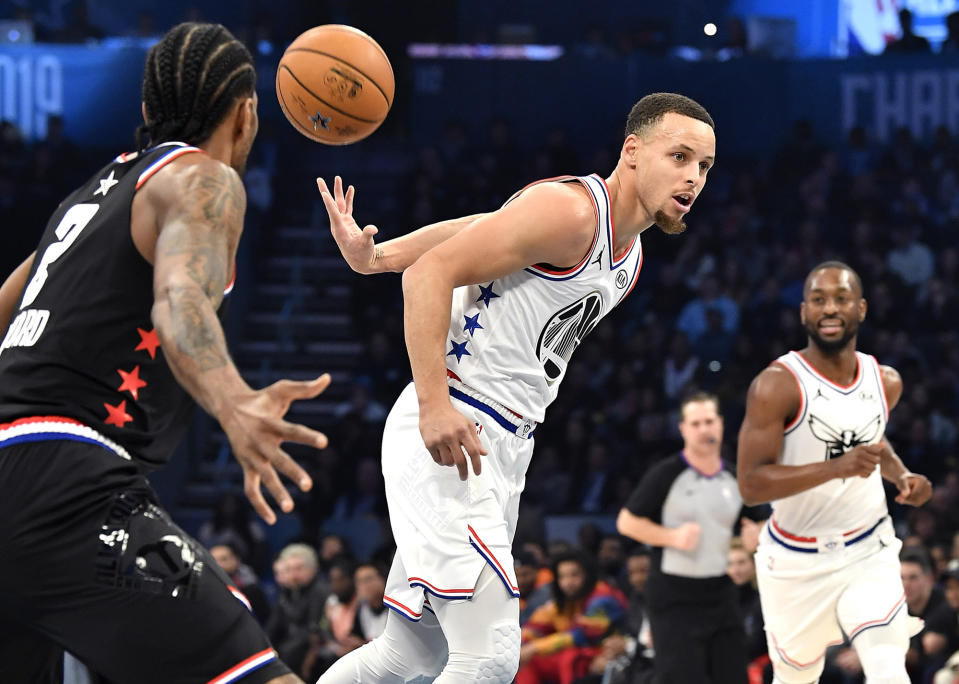 Golden State Warriors guard Stephen Curry throws a behind-the-back pass to a teammate on a fast break during the NBA 2019 All-Star Game. (Jeff Siner/Charlotte Observer/Tribune News Service via Getty Images)