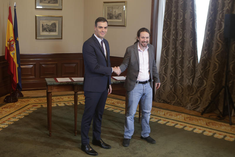 Spain's caretaker Prime Minister Pedro Sanchez, left, and Podemos party leader Pablo Iglesias shake hands before signing an agreement at the parliament in Madrid, Spain, Tuesday, Nov. 12, 2019. The leaders of Spain's Socialist party and the left-wing United We Can (Podemos) party say they have reached a preliminary agreement toward forming a coalition government. But the deal announced Tuesday won't provide enough votes in parliament for the Socialists, who won a general election, to take office without the support of other parties. (AP Photo/Paul White)