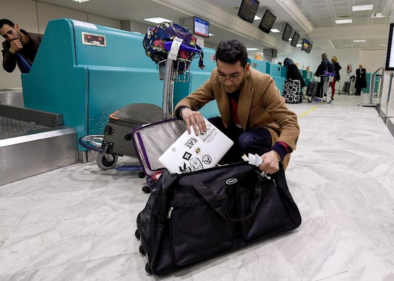A Libyan traveller packs his laptop in his suitcase before boarding his flight for London at Tunis-Carthage International Airport on March 25, 2017