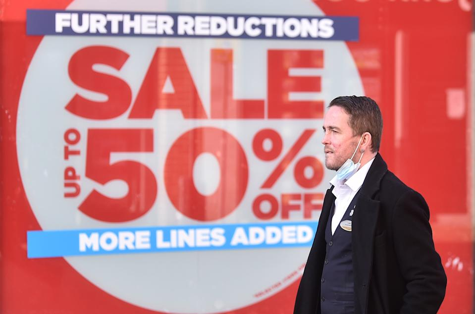 A man walks past a further reductions sale sign, displayed outside JD Sports shop window in Macclesfield , England. Photo: Nathan Stirk/Getty Images