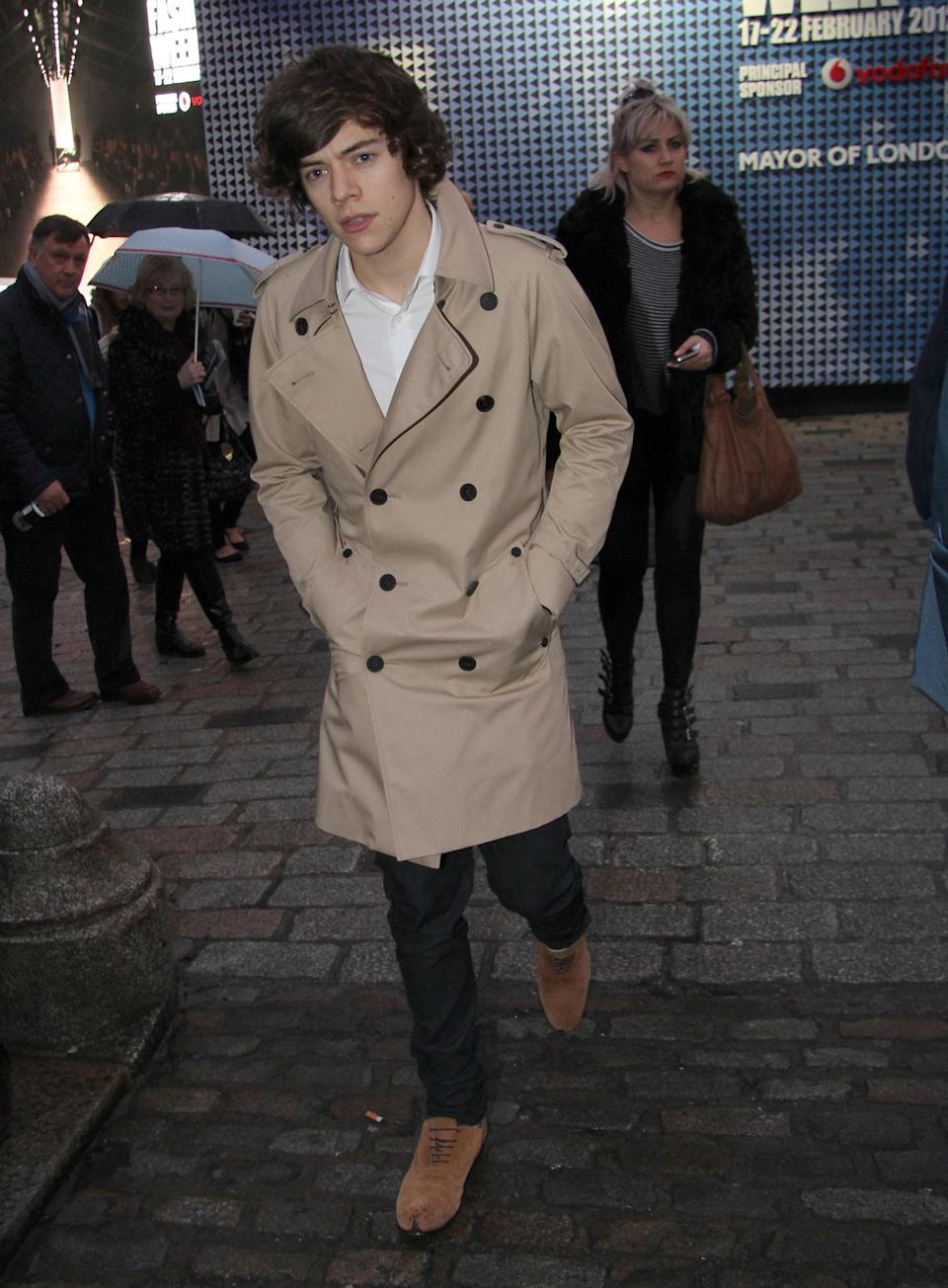 Harry hit up London Fashion Week in style in 2012 in a khaki trench, black skinnies, and tan suede shoes.