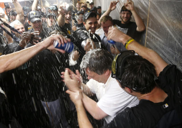 The Pittsburgh Pirates douse traveling secretary Greg Johnson with champaign and beer after a baseball game and 2-1 win over the Chicago Cubs Monday, Sept. 23, 2013, in Chicago. Johnson has been in his post for 30 years. (AP Photo/Charles Rex Arbogast)