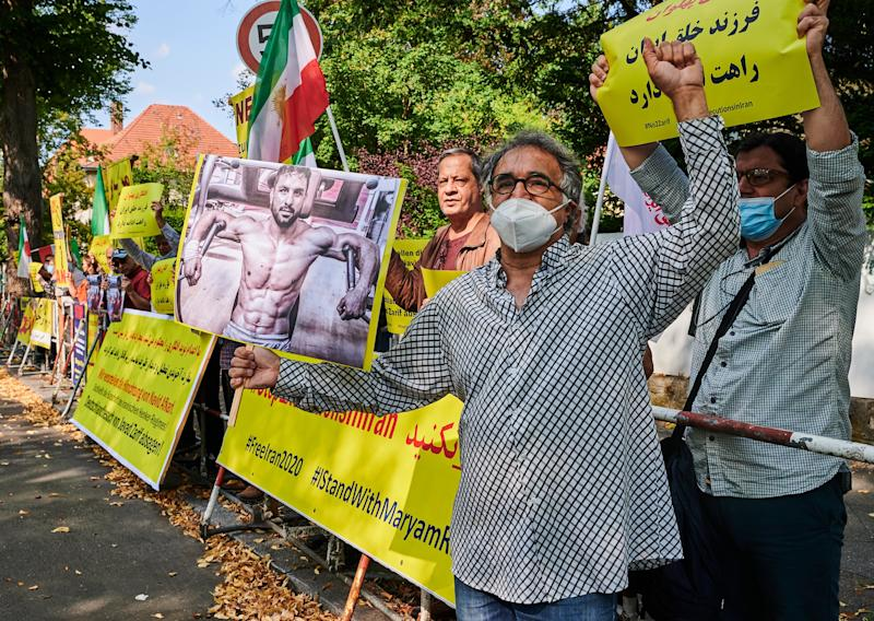 Demonstrators hold pictures of the executed wrestler Navid Afkari in front of the Iranian embassy.