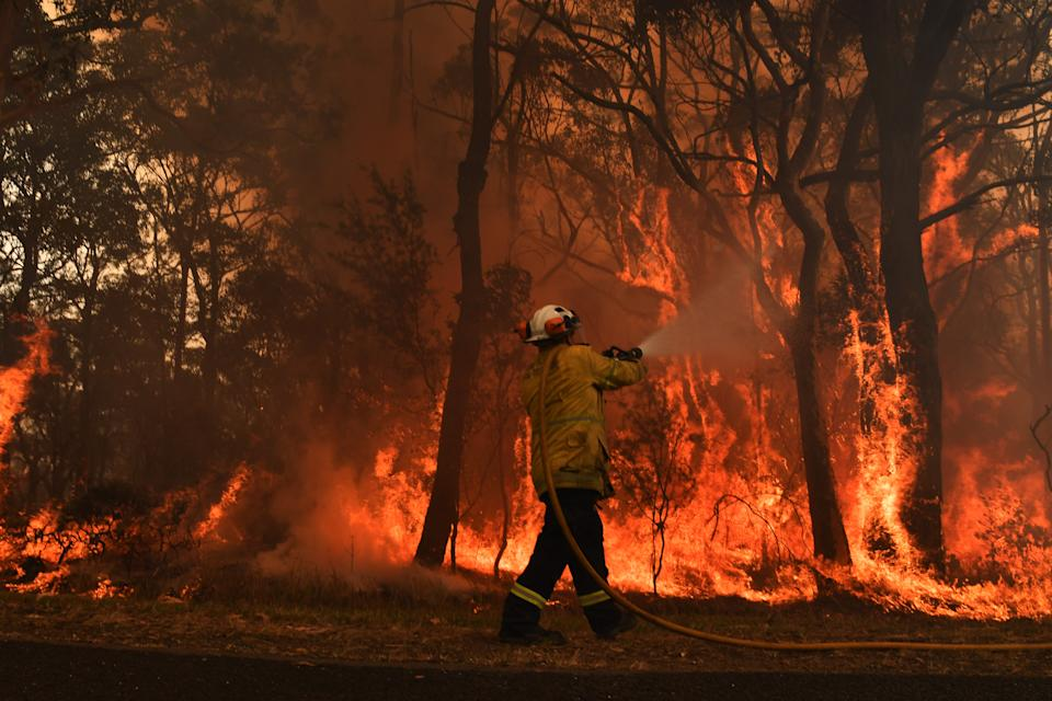 CENTRAL COAST, AUSTRALIA - DECEMBER 10: Rural Fire Service (RFS) firefighters fight a flare up on a containment line at the Three Mile Fire in the suburb of Kulnura on December 10, 2019 on the Central Coast, Australia. More than 80 bushfires are burning across New South Wales, and thousands of firefighters and aircraft on alert as temperatures are expected to soar above 40c. (Photo by Sam Mooy/Getty Images)