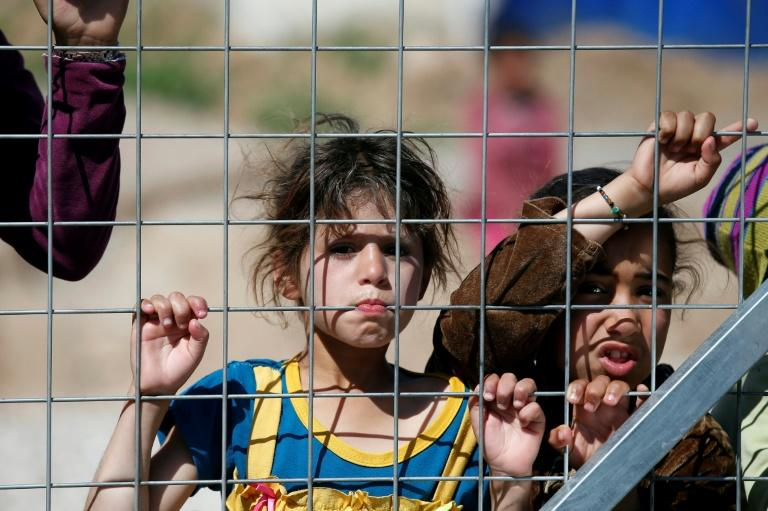 Iraqi children displaced from the battleground city of Mosul stand behind a fence at a camp in the village of Hasan Sham, 30 kilometres (18 miles) away