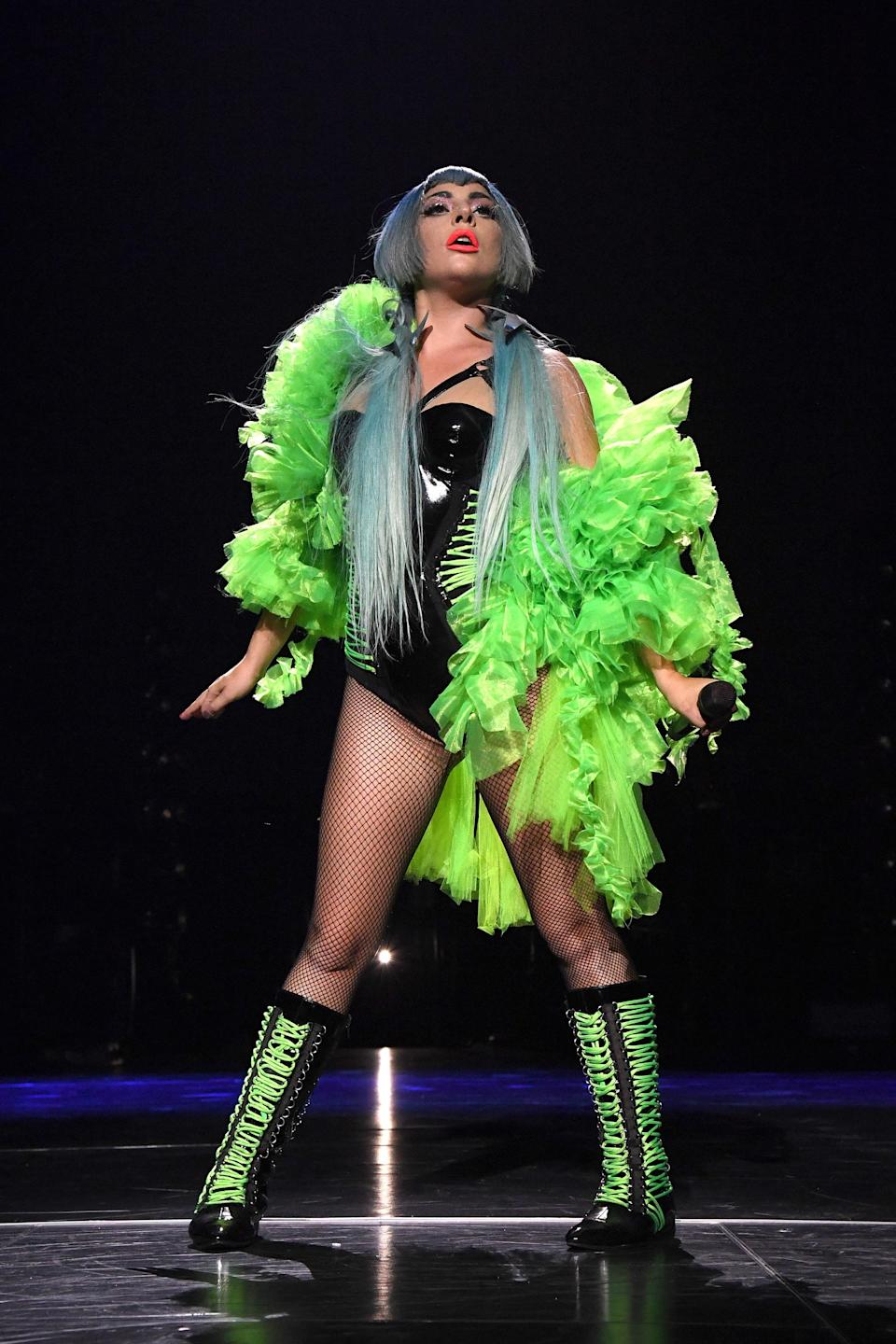 Who knew neon green feathers could be so fashionable? BRB, I will be wearing this to every club once they reopen.