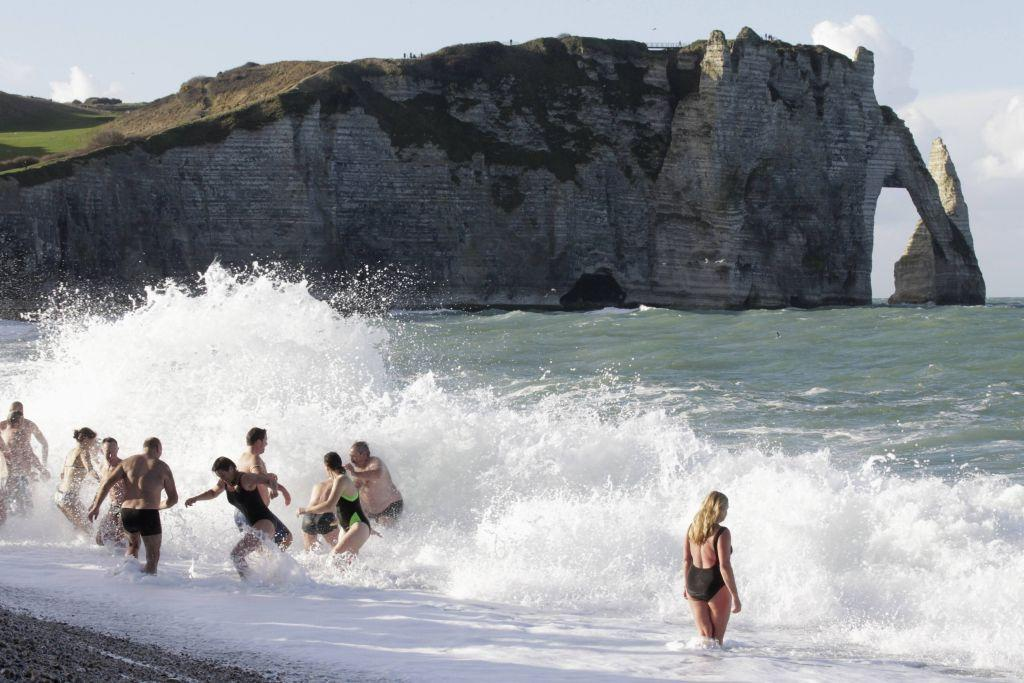 People participate in a traditional New Year's Day swim in front of the famous cliff at Etretat, western France January 1, 2013.