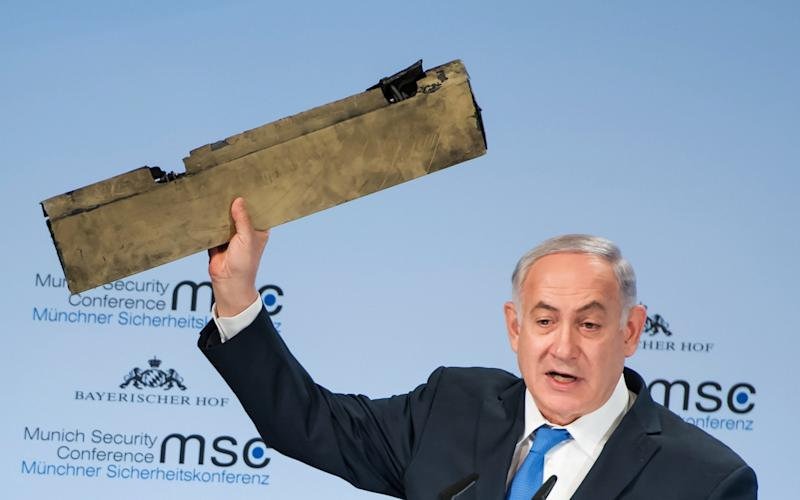 Israeli Prime Minister Benjamin Netanyahu holds up an object what he claimed was a piece of an Iranian drone shot down in Israeli airspace - AFP