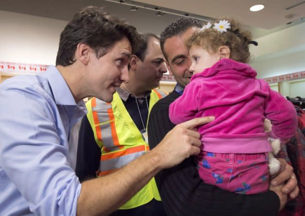 Prime Minister Justin Trudeau welcomed the first group of Canada's refugees at the welcome centre Dec. 11, 2015. Photo from the Canadian Press