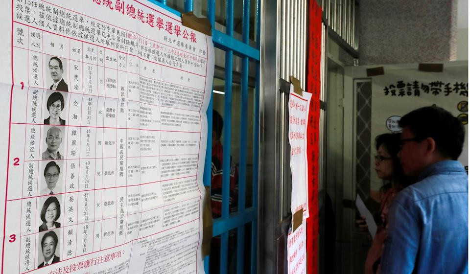 Voters consider election contenders at a polling station in New Taipei City, Taiwan, on Saturday. Photo: Reuters