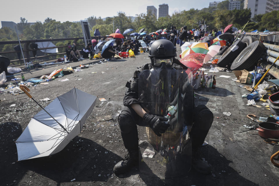 A pro-democracy protester with protection gears holds a bottle of molotov cocktail on a bridge outside the Chinese University campus in Hong Kong, Wednesday, Nov. 13, 2019. Police increased security around Hong Kong and its university campuses as they brace for more violence after sharp clashes overnight with anti-government protesters. (AP Photo/Ng Han Guan)