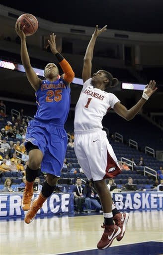 Florida forward Christin Mercer (25) drives to the basket as Arkansas forward Keira Peak (1) defends during the first half of an NCAA college basketball game at the Southeastern Conference tournament, on Thursday, March 7, 2013, in Duluth, Ga. (AP Photo/John Bazemore)