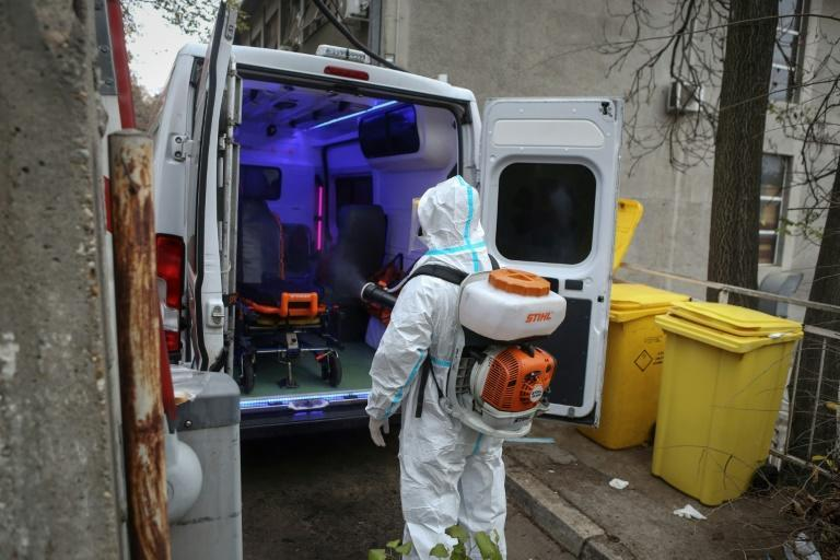 A medical worker disinfects an ambulance in Belgrade