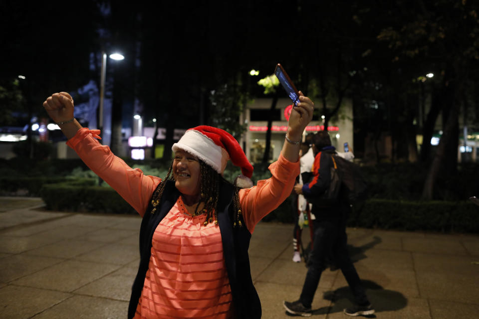 Lupita Rojo from Jalisco State celebrates the arrival of the new year, just after midnight on New Year's Day, Friday, Jan. 1, 2021. Although Mexico City cancelled its annual New Year's celebration to curb the spread of the COVID-19 pandemic, dozens of people came out in small groups to mark midnight with selfies and video calls from the iconic city landmark .(AP Photo/Rebecca Blackwell)
